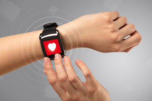 Female hand with smartwatch and with heart rate icon on the watch